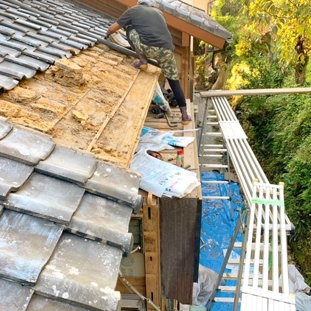 屋根の瓦をめくって土を降ろしています。